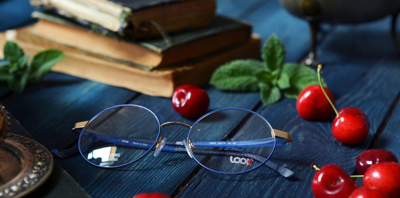 Niebieskie oprawki okularowe w tle wiśnie